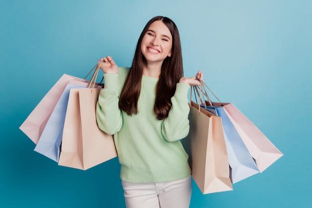 Senhora encantadora carregando sacolas de compras isoladas em fundo azul