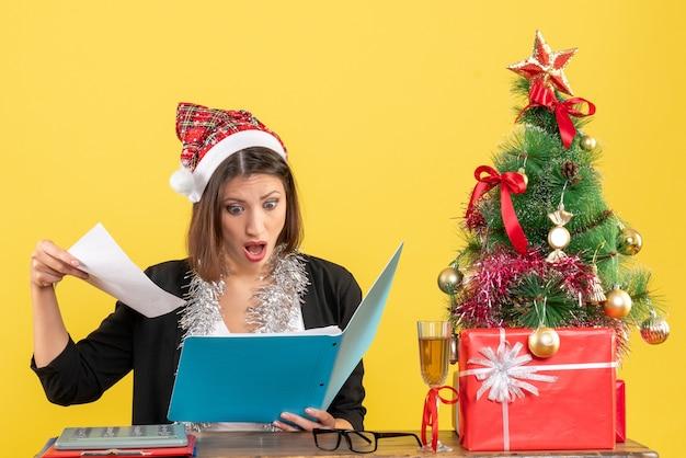Senhora encantadora chocada de terno com chapéu de papai noel e decorações de ano novo segurando documento no escritório em amarelo isolado