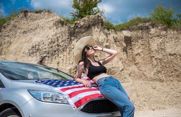Senhora encantadora com a bandeira dos eua perto do carro em uma pedreira de areia no verão