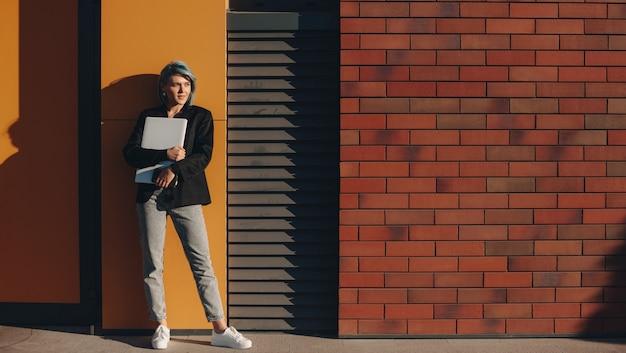 Senhora encantadora com cabelo azul posando em uma parede de tijolos em um dia ensolarado abraçando um computador