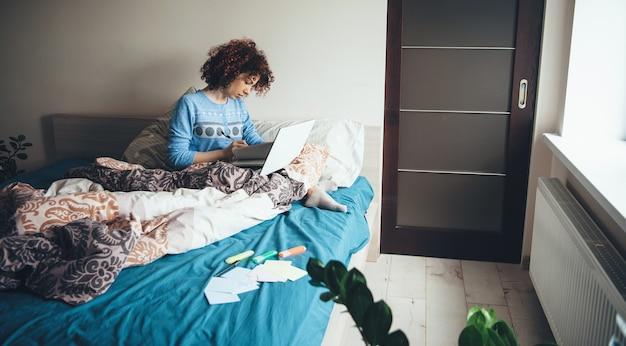 Senhora encantadora com cabelo encaracolado e pijama azul usando um laptop na cama enquanto faz o dever de casa