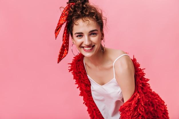 Senhora encantadora com casaco fofo posando em rosa