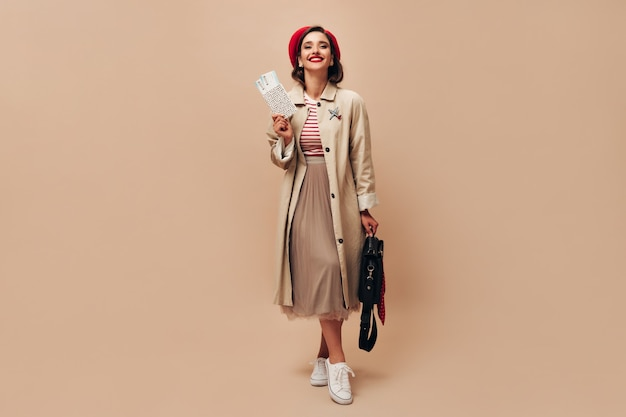 Senhora encantadora com chapéu vermelho e trincheira bege tem ingressos. mulher bonita em um elegante casaco longo e uma camisola listrada com bolsa preta posando.