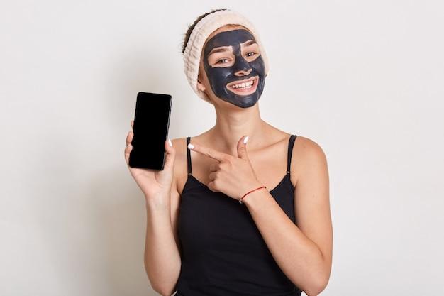 Senhora encantadora com máscara facial cosmética segurando um celular moderno nas mãos e apontando com o dedo indicador