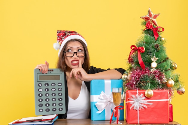 Senhora encantadora confusa de terno com chapéu de papai noel mostrando calculadora no escritório em amarelo isolado