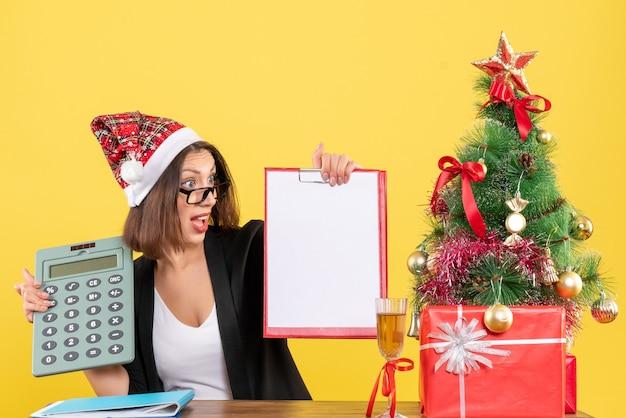 Senhora encantadora confusa de terno com chapéu de papai noel mostrando documento e segurando calculadora no escritório em amarelo isolado