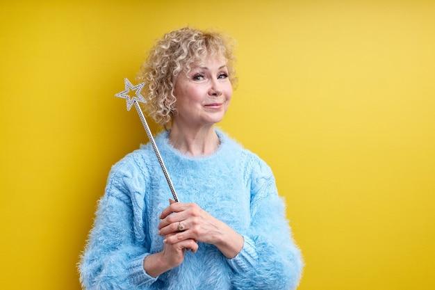 Senhora encantadora de 60 anos com varinha mágica nas mãos, olhando para a frente, posando com um lindo sorriso