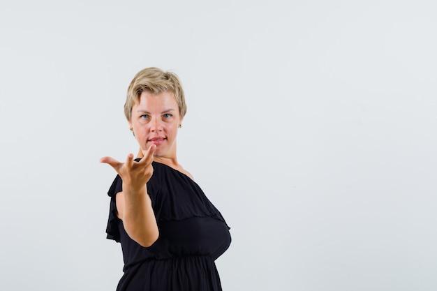 Senhora encantadora de blusa preta, levantando a mão.