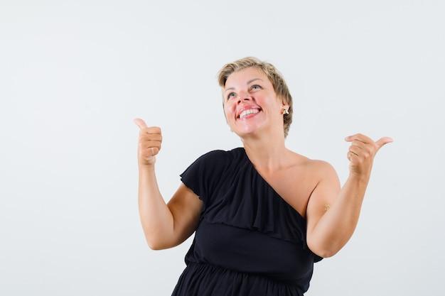 Senhora encantadora de blusa preta mostrando o polegar para cima e parecendo alegre