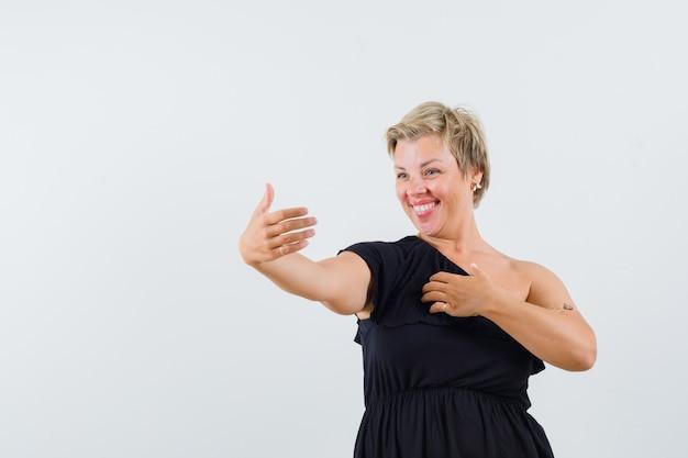 Senhora encantadora de blusa preta posando como se estivesse tirando uma selfie e parecendo alegre