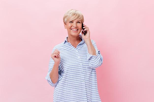 Senhora encantadora de camisa xadrez falando ao telefone e sorrindo no fundo rosa