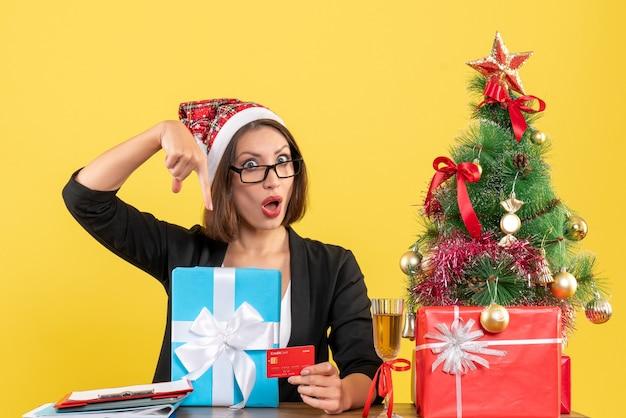 Senhora encantadora de terno com chapéu de papai noel e óculos apontando para presente e cartão de banco no escritório