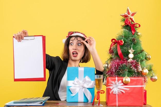Senhora encantadora de terno com chapéu de papai noel, verificando documentos, sentindo-se surpresa no escritório em amarelo isolado