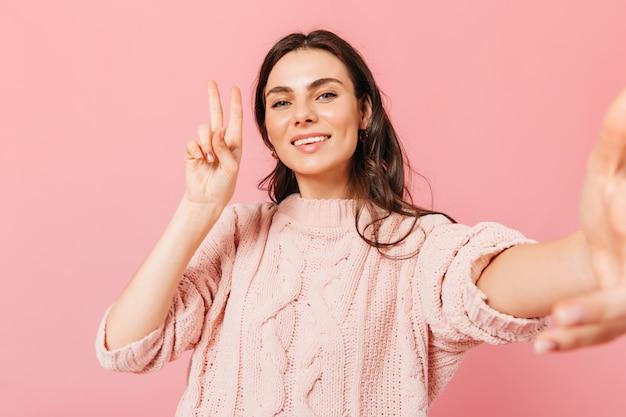 Senhora encantadora de vestido de malha faz selfie no fundo rosa. mulher de cabelos escuros em alto astral, mostrando sinal de paz.