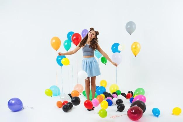 Senhora encantadora em roupas da moda parece feliz segurando bando de balão