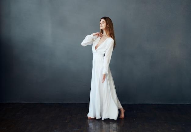 Senhora encantadora em um vestido branco sobre um fundo cinza dança gesticulando com seu modelo de mãos. foto de alta qualidade