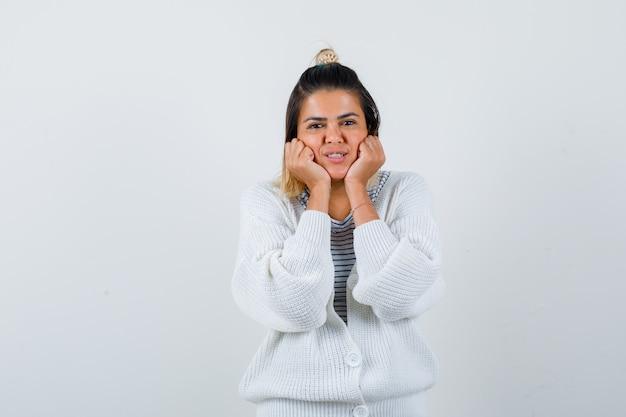 Senhora encantadora inclinando as bochechas nas mãos em t-shirt, casaco de lã e parecendo alegre.