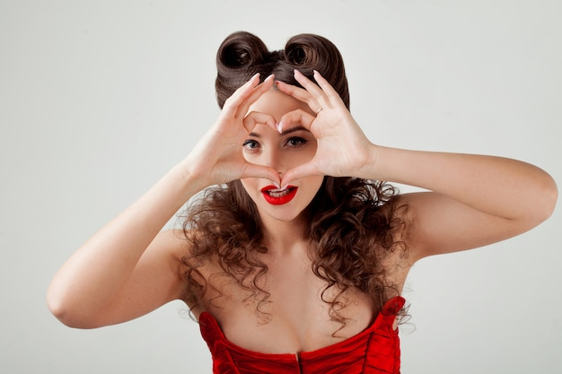 Senhora encantadora no espartilho vermelho, mostra sinal de coração