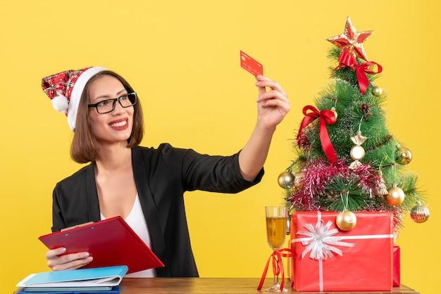 Senhora encantadora orgulhosa de terno com chapéu de papai noel e óculos mostrando o cartão do banco no escritório em amarelo isolado