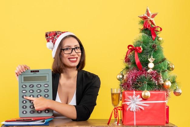Senhora encantadora satisfeita de terno com chapéu de papai noel e óculos mostrando calculadora no escritório em amarelo isolado