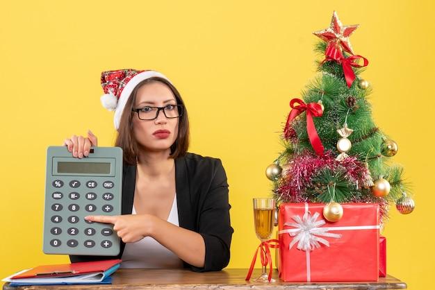 Senhora encantadora surpresa de terno com chapéu de papai noel e óculos mostrando calculadora no escritório em amarelo