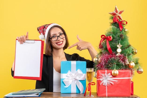 Senhora encantadora surpresa de terno com chapéu de papai noel olhando para documento apontando para ela mesma no escritório em amarelo isolado