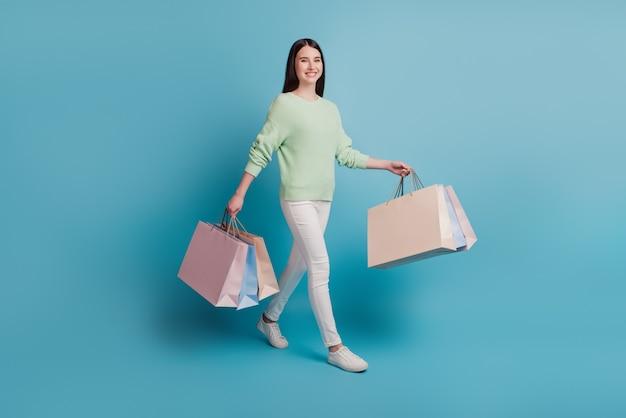 Senhora encantadora, vá carregar sacolas de compras isoladas em um fundo azul