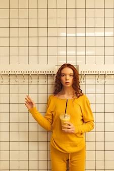 Senhora encaracolada concentrada jovem ruiva em pé no café