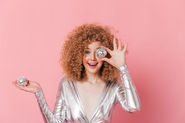 Senhora encaracolada de olhos azuis, vestida com top brilhante, posando com pequenas bolas de discoteca no espaço rosa.