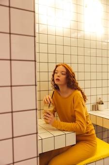 Senhora encaracolado ruiva jovem sério sentado no café