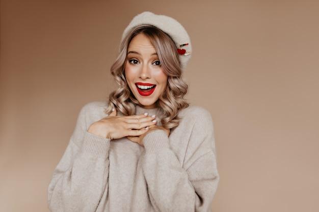 Senhora engraçada de olhos castanhos em um suéter fofo posando com um sorriso surpreso