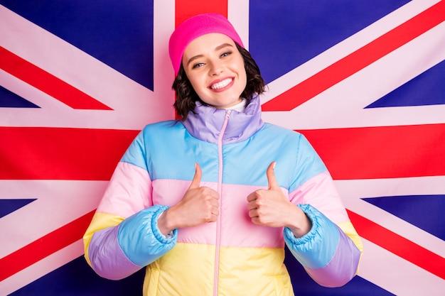 Senhora engraçada estudante de intercâmbio fazendo fotos no exterior para pais vestindo um casaco colorido quente com fundo rosa isolado