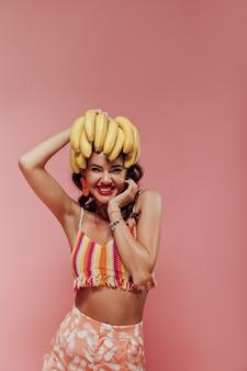 Senhora engraçada moderna com lábios vermelhos e cabelo encaracolado, em um top listrado e calças com estampa de abacaxi, sorrindo e posando com bananas.