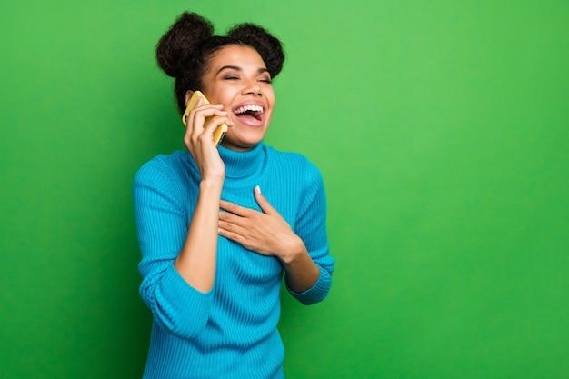 Senhora engraçada pele morena animada segurando o telefone falando