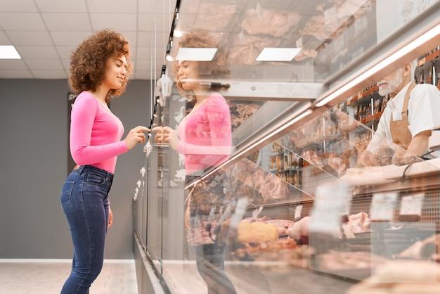 Senhora escolhendo carne crua atrás do balcão.