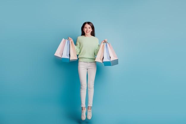 Senhora espantada a pular e carregar sacolas de compras isoladas em fundo azul