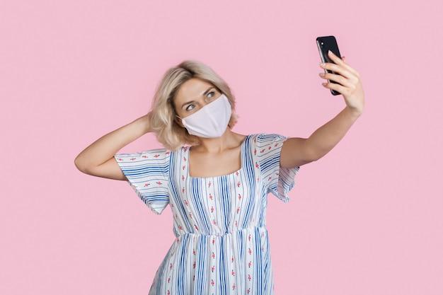 Senhora está fazendo uma selfie em uma parede rosa enquanto usa uma máscara