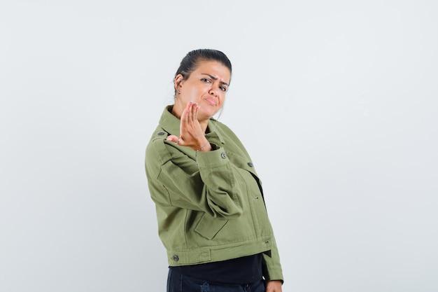 Senhora esticando a mão em gesto de perplexidade com jaqueta