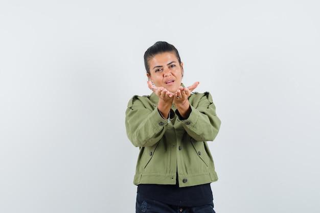 Senhora esticando as mãos em concha na jaqueta