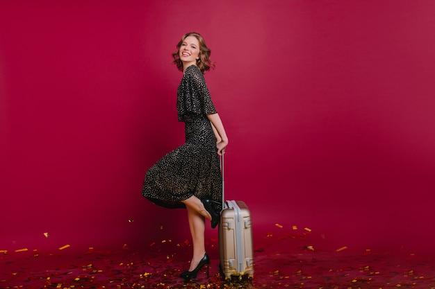Senhora europeia inspirada com bagagem pronta para viajar nas férias