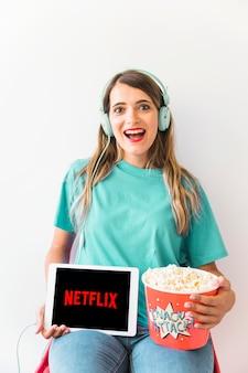Senhora excitada com pipoca e tablet com o logotipo da netflix