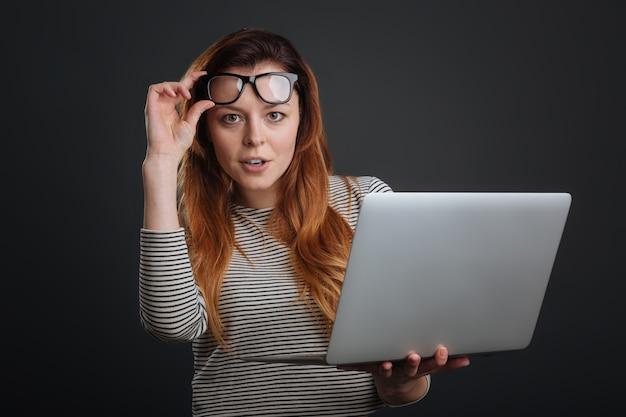 Senhora experiente. mulher jovem e bonita e inteligente usando o laptop e segurando os óculos em pé, isolado no fundo cinza