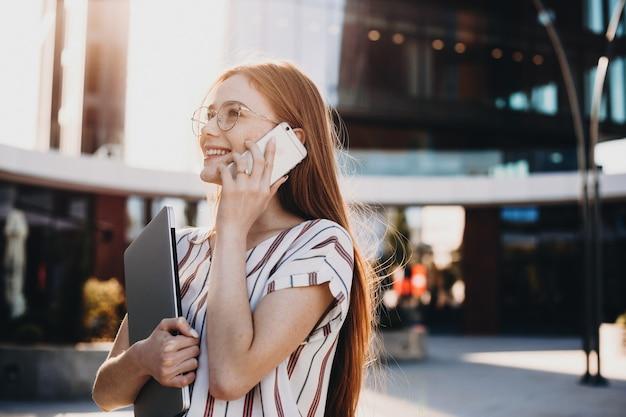 Senhora falando com alguém usando um celular