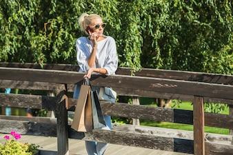 Senhora falando no smartphone na passarela