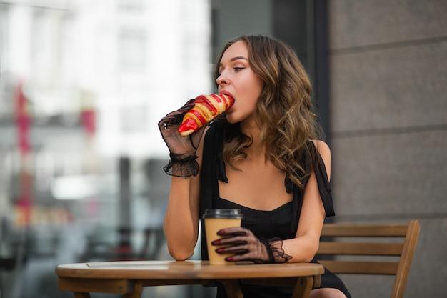 Senhora faminta tomando café da manhã com croissant em um café