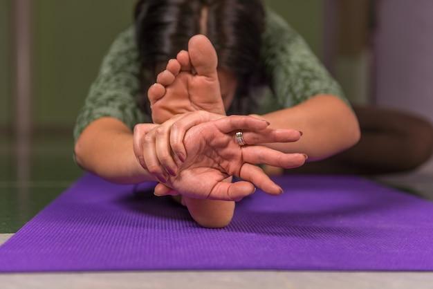 Senhora fazendo alongamentos de ioga em um estúdio