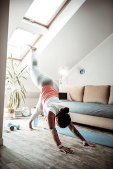 Senhora fazendo flexões. mulher encaracolada de pele escura levantando as pernas antes de virar no meio da sala