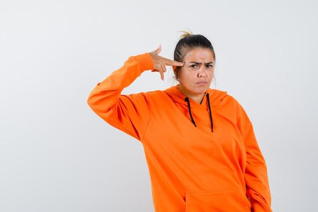 Senhora fazendo gesto de suicídio em um capuz laranja e parecendo séria