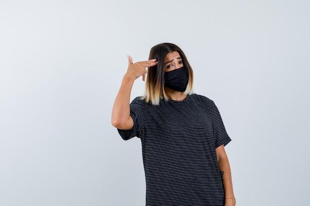 Senhora fazendo gesto de suicídio em vestido preto, máscara médica e parecendo deprimida. vista frontal.