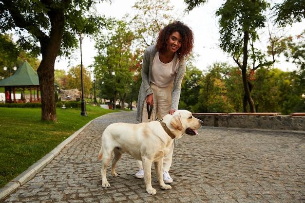 Senhora feliz, abraçando seu cachorro amigável branco enquanto caminhava no parque